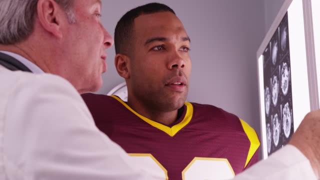 vídeos y material grabado en eventos de stock de medical doctor showing x-rays to college sports athlete - cuello humano