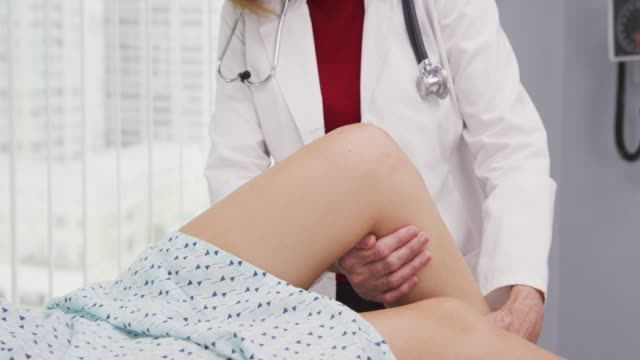 vídeos de stock, filmes e b-roll de medical doctor tending to young womans sprained knee injury at clinic - physical injury