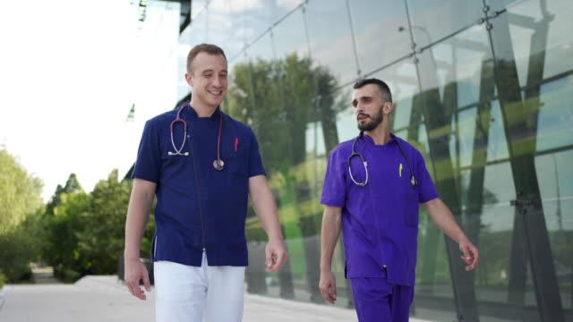 ärzte sprechen beim verlassen des krankenhauses nach der arbeit - ruhen stock-videos und b-roll-filmmaterial