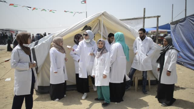 medical equipe near the israeli border fence, east of gaza city in the central gaza strip on april 13, 2018. several thousand gazans gathered for a... - 2018 gaza border protests stock videos & royalty-free footage