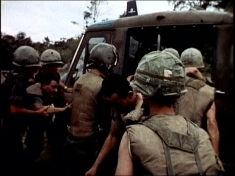 medical helicopter landing / soldiers helping wounded onto helicopter / soldiers carrying wounded man on stretcher / helicopter lifting off and... - vietnam war stock videos & royalty-free footage