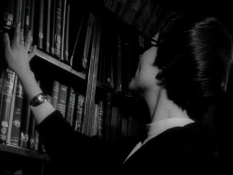 a medical librarian selects a book from a shelf and hands it to a customer 1958 - book stock videos & royalty-free footage