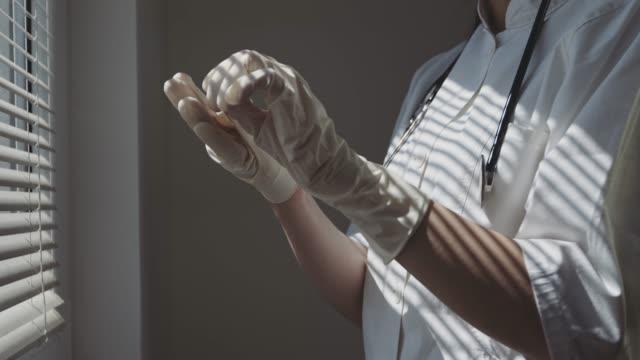 vídeos de stock e filmes b-roll de medical nurse puts medical gloves on by the window. stock video - estado médico