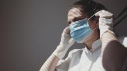 A medical nurse puts on a face a medical mask. 4k stock video