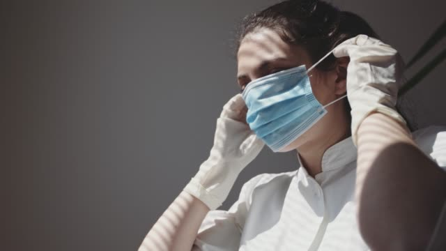 a medical nurse puts on a face a medical mask. 4k stock video - surgical mask stock videos & royalty-free footage