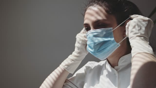 a medical nurse puts on a face a medical mask. 4k stock video - applying stock videos & royalty-free footage
