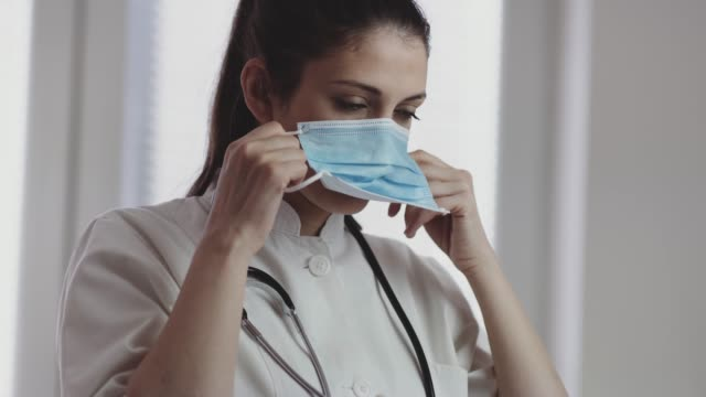 a medical nurse puts on a face a medical mask. 4k stock video - stetoscopio video stock e b–roll
