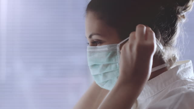 a medical nurse puts on a face a medical mask.  stock video - clinica medica video stock e b–roll