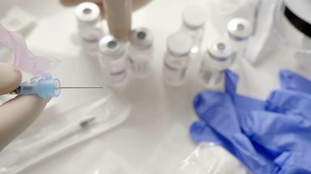 medico personale che prepara il vaccino covid-19 per il suo uso - preparation video stock e b–roll