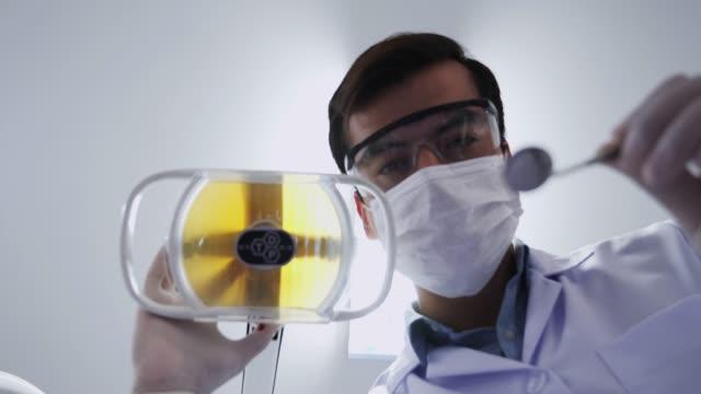 stockvideo's en b-roll-footage met medisch personeel op het werk in de tandheelkundige kliniek, lage hoek shot, geduldige oogpunt - elektrische lamp