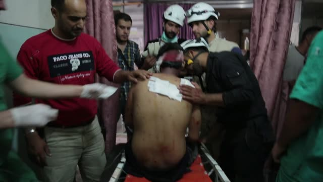 medical personnel bandage the back of an injured firefighter in a makeshift hospital in aleppo syria on june 22 2014 the man is a member of the... - makeshift stock videos and b-roll footage
