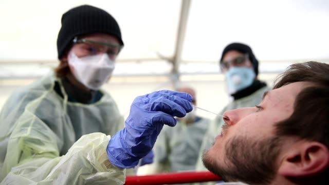 medical personnel demonstrate taking nose and throat mucous samples for coronavirus testing at a new outdoor facility for testing medical and... - människohals bildbanksvideor och videomaterial från bakom kulisserna