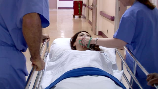 stockvideo's en b-roll-footage met medical personnel in hospital with patient - ziekenhuisbed
