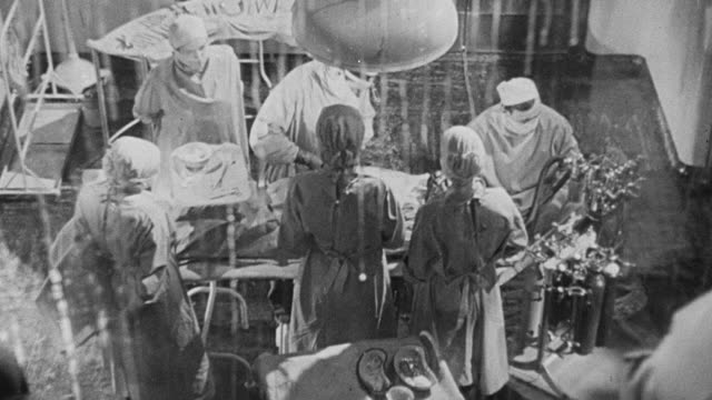 1948 ZI Medical personnel surrounding a patient while performing surgery / Kingham, England, United Kingdom