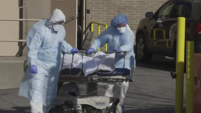 medical personnel wearing full protective gear transport two bodies on stretchers from new york's wyckoff heights medical center to a refrigerated... - stretcher stock videos & royalty-free footage