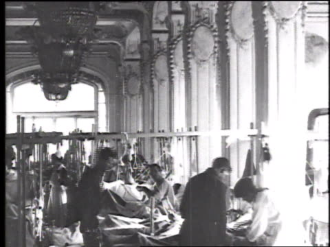 medical personnel work on patients lying in beds in a long light filled hospital ward / france - 1918 stock videos & royalty-free footage
