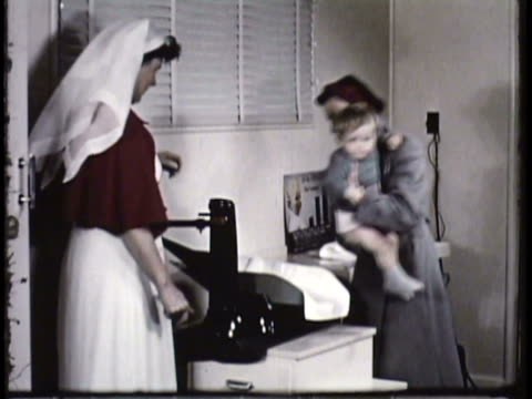 1955 MONTAGE WS MS CU PAN Medical practitioner weighing baby boy at doctor's office, nurses walking on sidewalk outside hospital building / New Zealand / AUDIO