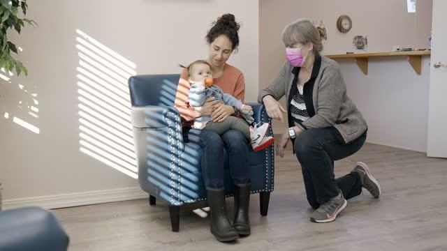 vídeos de stock, filmes e b-roll de profissional médico em rosto protetor recebendo novo paciente em sala de espera de consultório odontológico ou médico - clínica médica