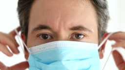 Medical professional putting on a safety face mask to prevent from corona virus