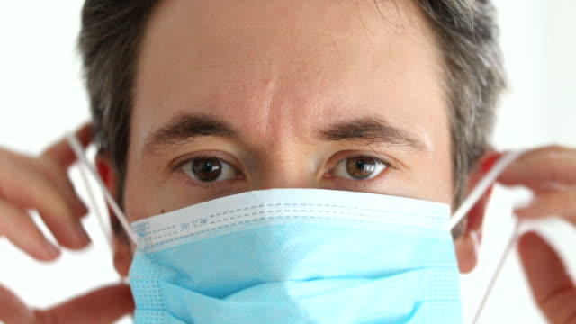 medical professional putting on a safety face mask to prevent from corona virus - surgical mask stock videos & royalty-free footage