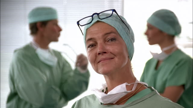 A medical professional smiles for the camera as two colleagues talk behind her.