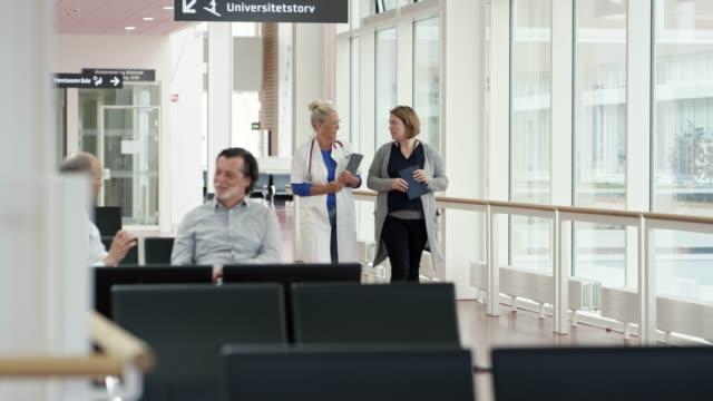 vídeos de stock e filmes b-roll de medical professionals and patient in corridor - corredor caraterística de construção