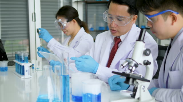 medical research scientists on modern laboratory with scientists conducting experiments. - campione di laboratorio video stock e b–roll