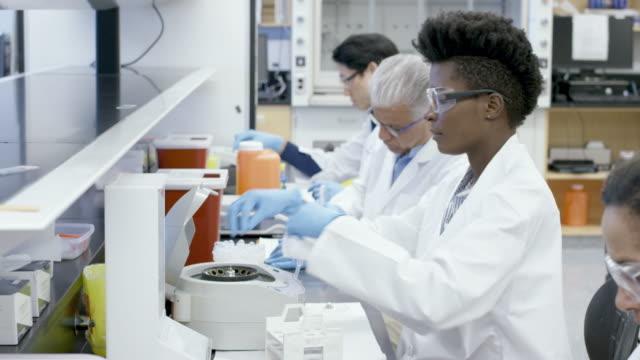medical researcher loading centrifuge - centrifuge stock videos & royalty-free footage