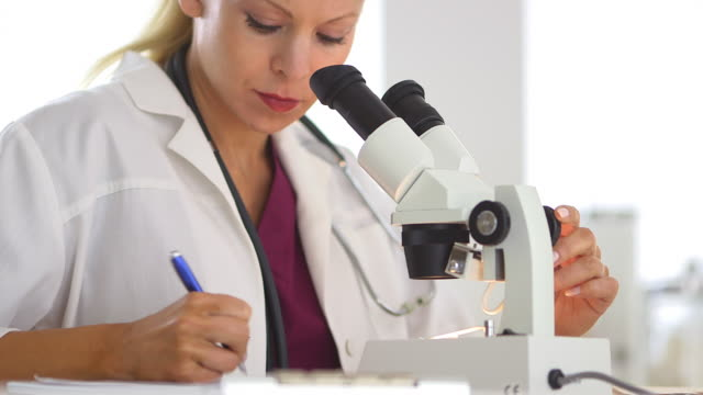 Medical researcher using microscope and writing notes