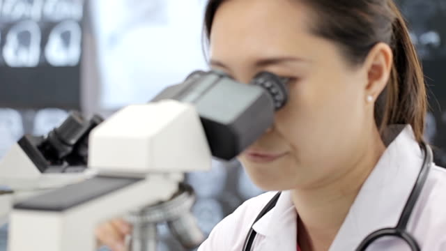 Medical researcher using microscope in laboratory