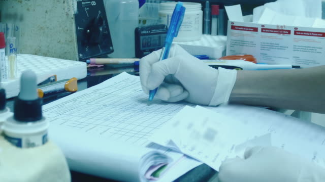 Medical researcher using pen writing notes