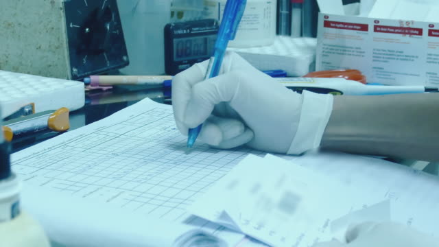 medical researcher using pen writing notes - clinic stock videos and b-roll footage