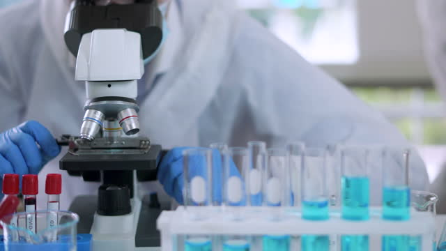 medical scientist looking at sample under microscope - clinic stock videos & royalty-free footage