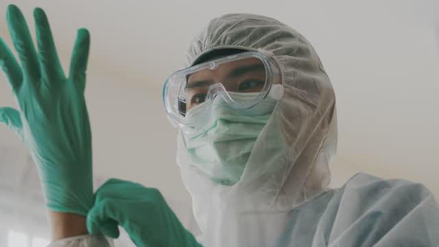 mediziner im schutzanzug ziehen handschuhe an - schutzbrille stock-videos und b-roll-filmmaterial