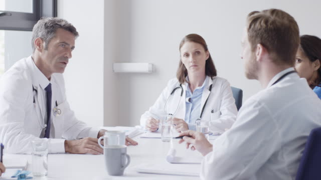 medical staff discussing at conference table - talking stock videos & royalty-free footage