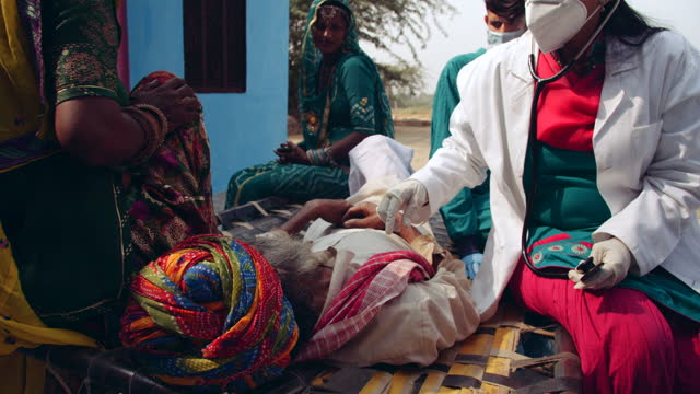 medical staff doctor healthcare worker visit a rural house during  pandemic to check on a senior adult male lying on his bed being cared by his family members in rural india because of disease and old age - india stock videos & royalty-free footage