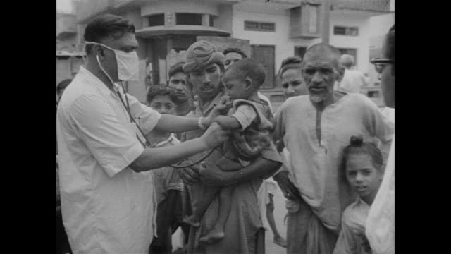vídeos de stock, filmes e b-roll de medical staff in india check babies and children for health issues at outdoor clinic - máscara cirúrgica