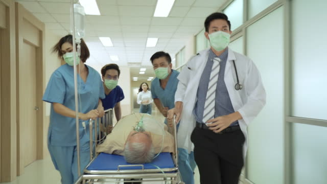 medical staff moving urgent patient in hospital hallways to emergency room - thai ethnicity stock videos & royalty-free footage