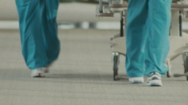 medical staff walks away from camera wearing hospital scrubs and sneakers pushing a gurney. - krankenhaus rollbett stock-videos und b-roll-filmmaterial