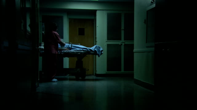 medical staff wheels a patient along a dim hospital corridor. - hospital trolley stock videos & royalty-free footage