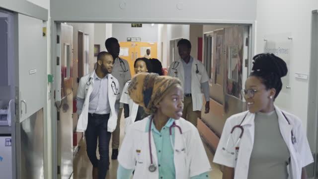 vidéos et rushes de l'équipe d'étudiants en médecine marchant dans le couloir d'hôpital - satisfaction