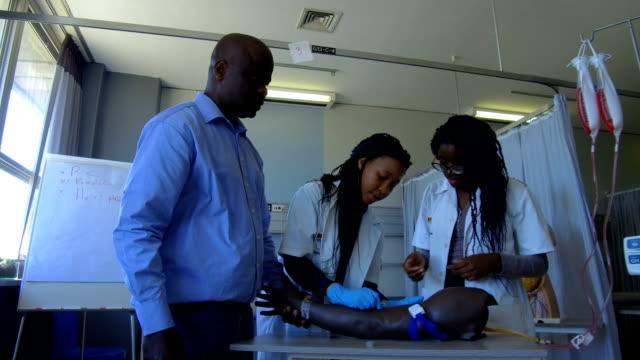 vídeos de stock, filmes e b-roll de treinamento para fazer injeções de estudantes de medicina - estudante universitária