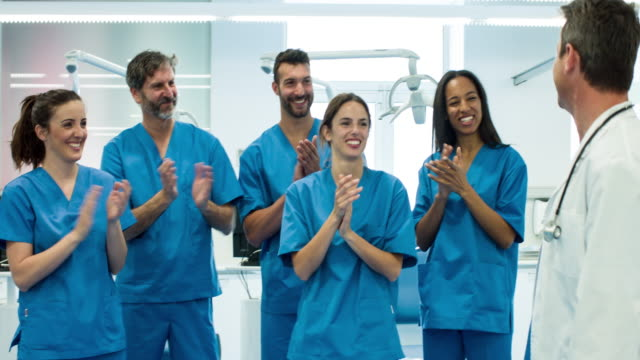 Medical team applauding doctor after a successful day