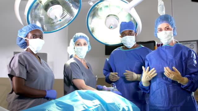 medizinisches team im operationssaal - op mundschutz stock-videos und b-roll-filmmaterial