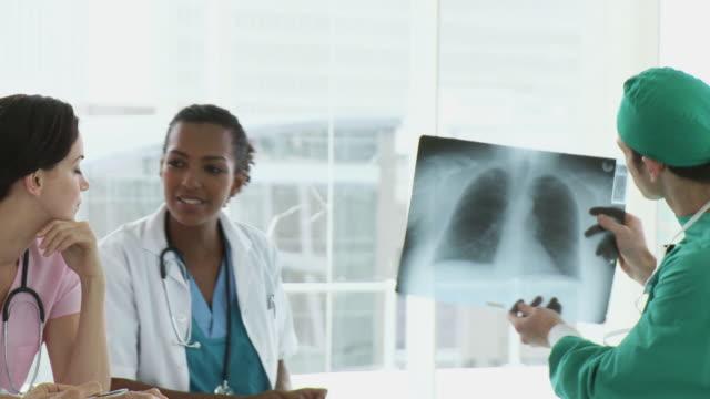 vídeos de stock e filmes b-roll de ms pan medical team looking at x-ray / cape town, western cape, south africa - bata cirúrgica