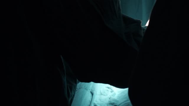 stockvideo's en b-roll-footage met medische team uitvoeren van chirurgische ingreep in moderne operationele room.multi etnische chirurgisch team in beschermende kleding uitvoeren van chirurgie ziekenhuis operatiekamer - elektrische lamp