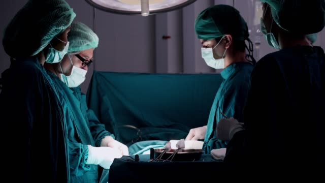 vídeos de stock e filmes b-roll de medical team performing surgical operation in modern operating room.multi ethnic surgical team in protective clothing performing surgery hospital operating theatre - cirurgia