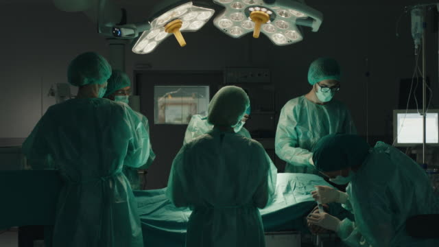 medical team performing surgical operation - operating stock videos & royalty-free footage