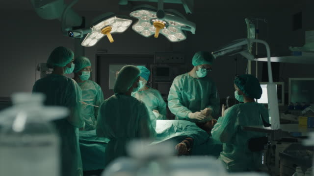 medical team performing surgical operation - operating theatre stock videos & royalty-free footage