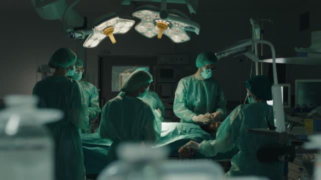 medizinisches team, das einen chirurgischen eingriff durchführt - op mundschutz stock-videos und b-roll-filmmaterial